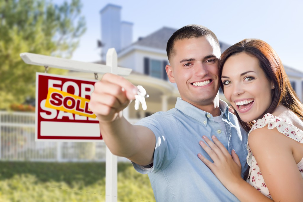 Couple In Front of New Home with New House Keys and Sold Real Estate Sign Outside.